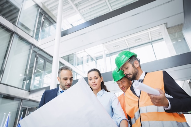 Businessman discussing on blueprint with architects Free Photo