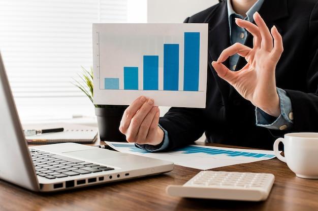 Uomo d'affari che fa il segno giusto mentre si tiene il grafico di crescita Foto Gratuite