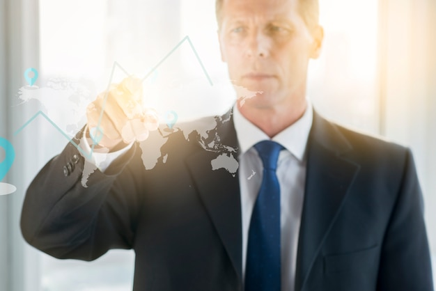 Businessman drawing graph on transparent glass board Free Photo