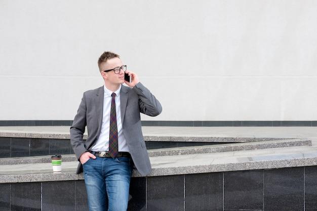 灰色のジャケット、ブルージーンズ、白いシャツ、ネクタイに身を包んだビジネスマンは、ビジネスセンター、コーヒーを飲む、電話で話している近くで昼休みを持っています。 Premium写真