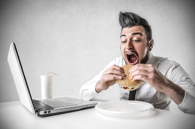Businessman eating hamburger Premium Photo