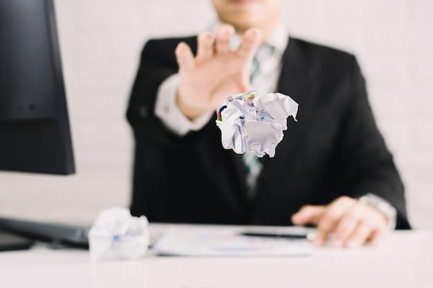 Эмоции бизнесмена и концепция терпеть неудачу скомкали бумагу на таблице с, несчастной никакая идея к думать бросая бумаги в офисе Premium Фотографии