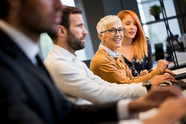 Businessman executive in group meeting with other businessmen and businesswomen in modern office with  computer Premium Photo