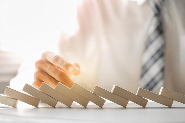 ビジネスマンは木製のブロックのドミノ効果を停止しようとして失敗しました。 Premium写真