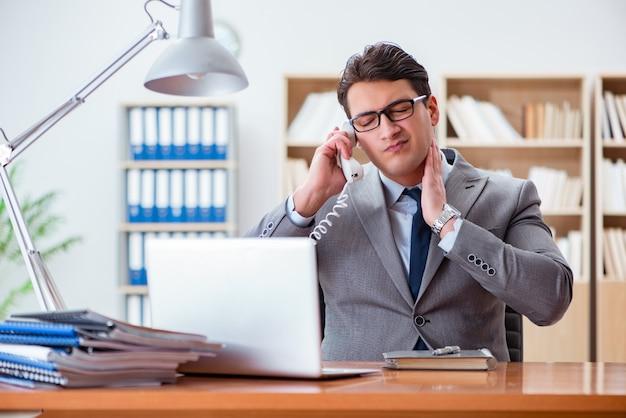 Бизнесмен чувствует боль в офисе Premium Фотографии