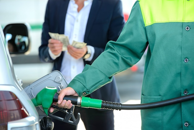 Businessman give money dispensers, filled car on gas station Premium Photo