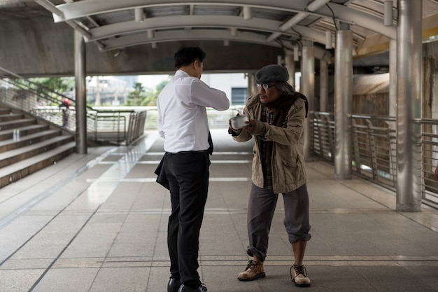 Businessman give money to old homeless Premium Photo