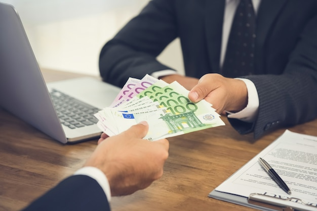 Businessman giving money, euro banknotes, to his partner while making contract Premium Photo