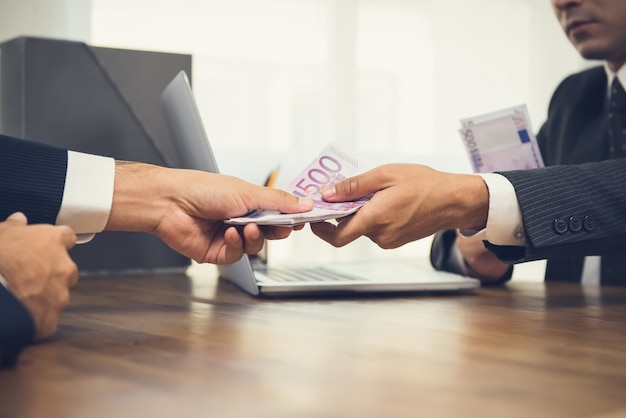Businessman giving money, euro banknotes, to his partner on working desk Premium Photo