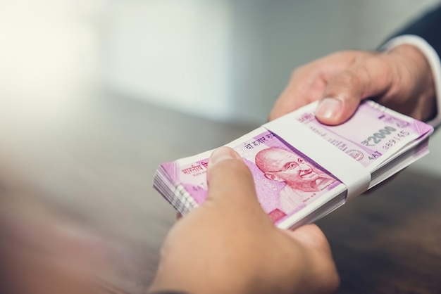 Businessman giving money, indian rupee currency, to his partner   Premium Photo