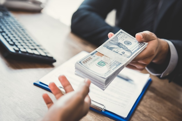 Businessman giving money, us dollars, to his partner while making contract Premium Photo