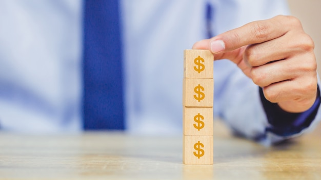 Businessman hand arranging wood block with icon money dollar for investment concept Premium Photo