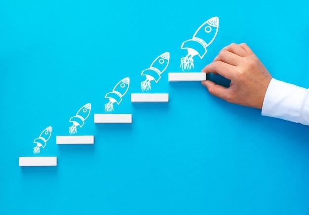 ロケットを描くとステップ階段として積み重ねて木製のブロックを配置するビジネスマンの手 Premium写真