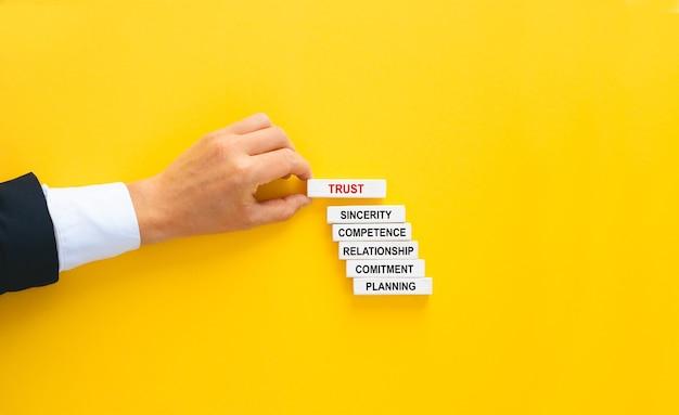 信頼の概念を持つビジネスマンの手造りの木製ブロック。 Premium写真