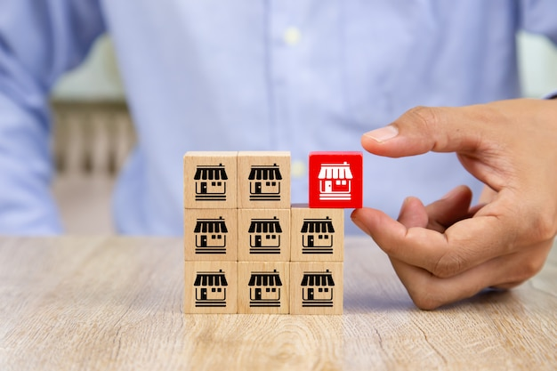 Businessman hand choose wooden blog with franchise marketing icons store. Premium Photo