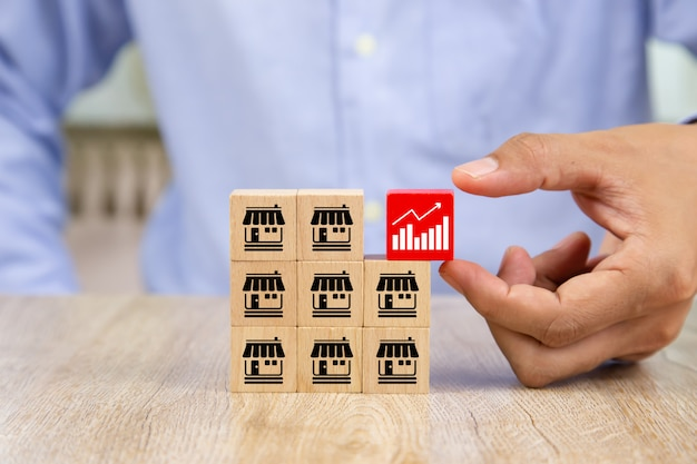 Businessman hand choose wooden blog with graph icon. Premium Photo