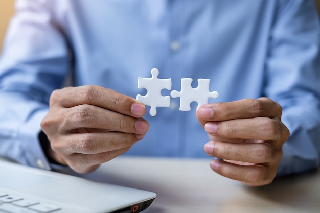 Businessman hand connecting couple puzzle piece in office. Premium Photo