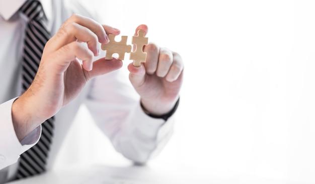 Бизнесмен рука подключения головоломки. бизнес-решения, успех и концепция стратегии. Premium Фотографии