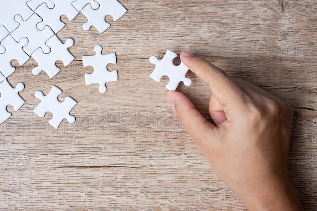 Businessman hand connecting  puzzle piece. business solutions, mission target, successful, goals, cooperation, partnership and strategy Premium Photo