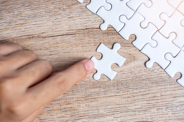 Businessman hand connecting  puzzle piece. business solutions, mission target Premium Photo