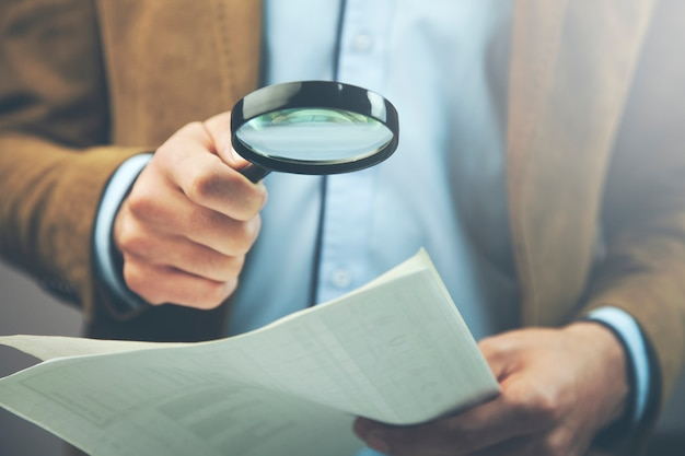 Businessman hand document and magnifier