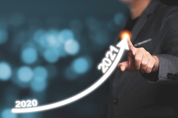 Бизнесмен рука рисунок стрелка тенденции увеличения с 2020 по 2021 год. это символ концепции роста инвестиций в бизнес. Premium Фотографии