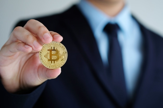 Businessman hand holding bitcoins, close up, cryptocurrency and blockchain concept Premium Photo