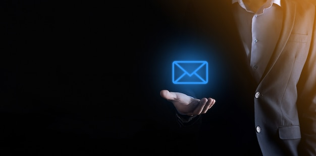 Businessman hand holding e-mail icon, contact us by newsletter email and protect your personal information Premium Photo