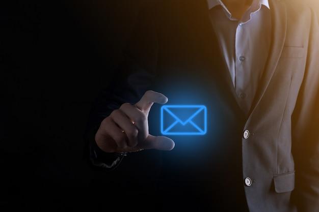 Businessman hand holding e-mail icon Premium Photo