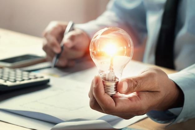 Businessman hand holding lightbulb in office. Premium Photo