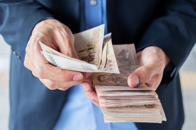 Businessman hand holding thai baht banknote stack. Premium Photo