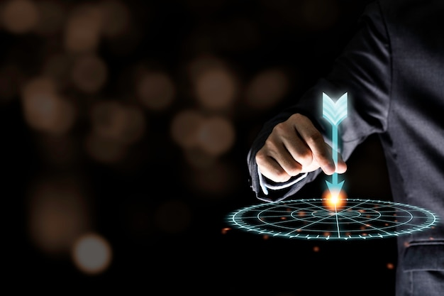 Businessman hand holding and throwing virtual dart to target board on black wall.business and investment target concept. Premium Photo