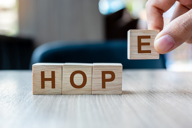 Businessman hand holding wooden cube block with hope business word on table background. Premium Photo