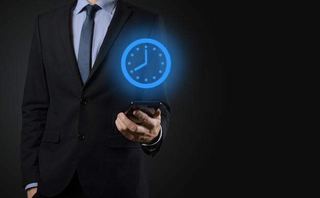 Рука бизнесмена держит значок часов часов со стрелкой. оперативное выполнение работы Premium Фотографии