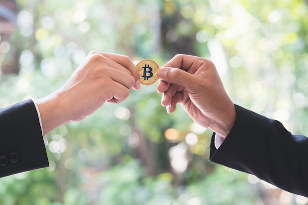 Businessman hand passing cryptocurrency golden bitcoin coin in office. Premium Photo