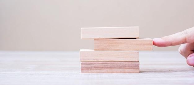 塔に木製のブロックを配置または引っ張って実業家の手。 Premium写真