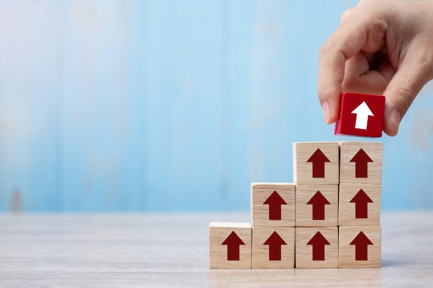 Businessman hand placing or pulling red block with arrow and growth up arrow on table Premium Photo