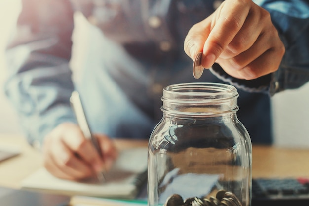 Businessman hand puting coins into jug glass Premium Photo