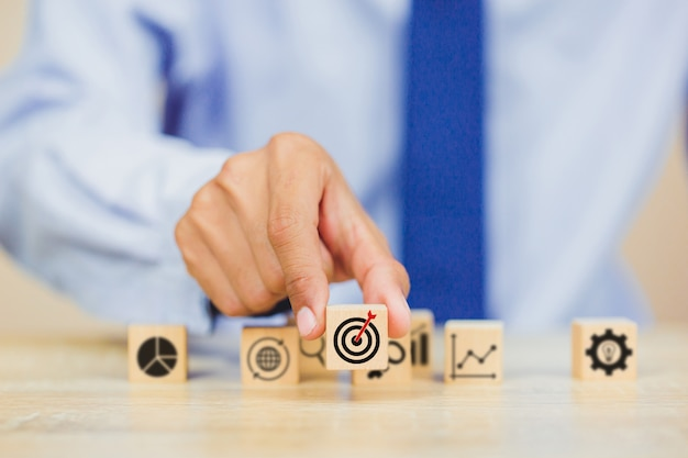 Businessman hand putting wood cube block on top with target success concept. Premium Photo