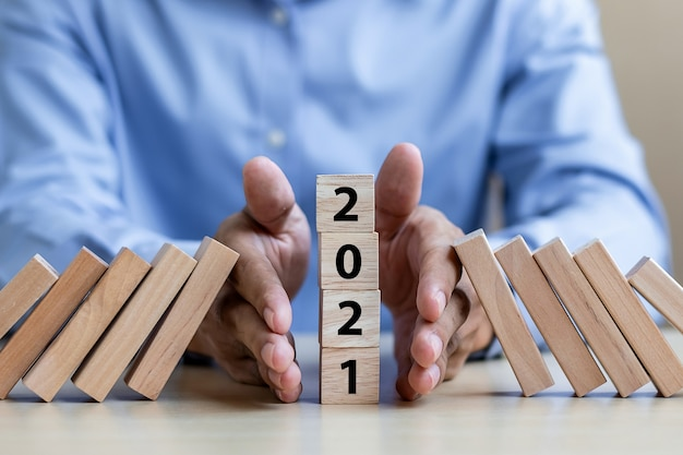 Businessman hand stopping falling of 2021 Premium Photo