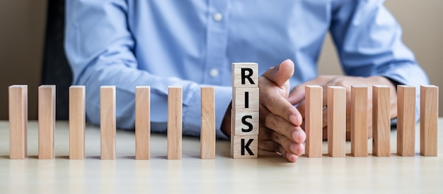 Businessman hand stopping falling wooden blocks or dominoes. Premium Photo