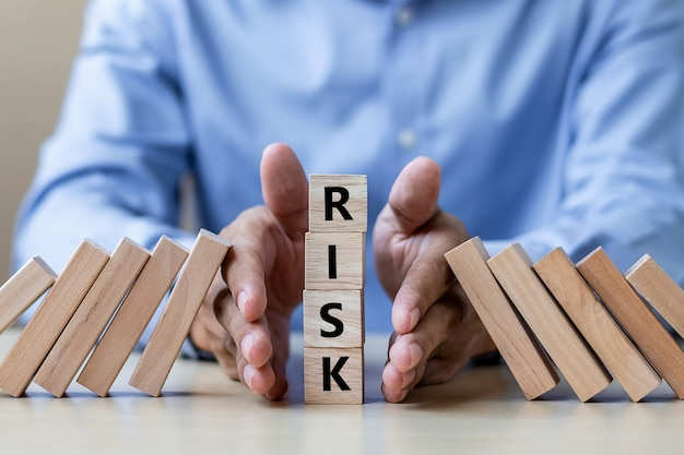 Businessman hand stopping falling wooden blocks or dominoes Premium Photo