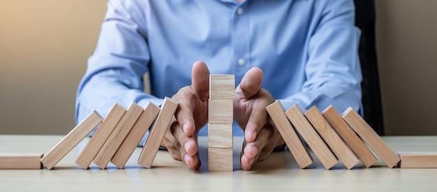 Рука бизнесмена останавливая падающие деревянные блоки или домино Premium Фотографии