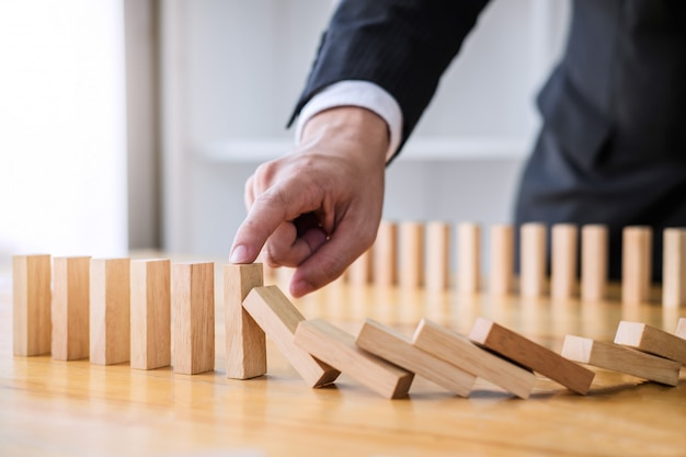 Businessman hand stopping falling wooden dominoes effect from continuous toppled or risk Premium Photo