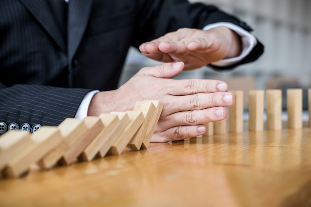 Businessman hand stopping falling wooden dominoes effect Premium Photo