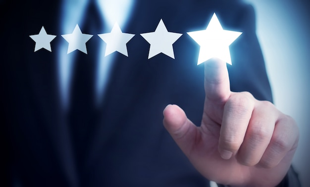 Businessman hand touching five star review to increase rating of company concept Premium Photo