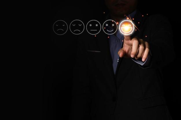 実業家の手が黒い背景に笑顔感情気分アイコンに触れます。市場・顧客サービスからの満足度調査です。 Premium写真