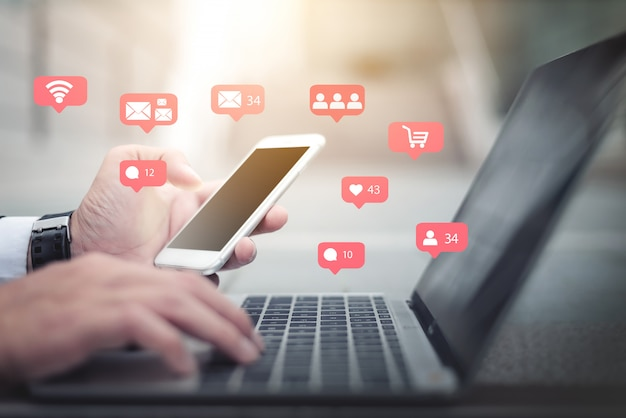 Businessman hand using mobile phone and laptop. business concept. Premium Photo