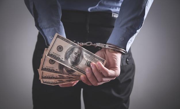 Businessman in handcuffs holding dollar banknotes. corruption Premium Photo