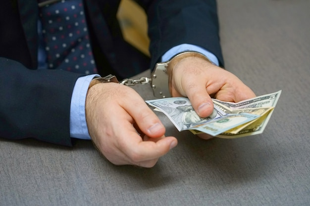 Businessman in handcuffs with a bribe Premium Photo